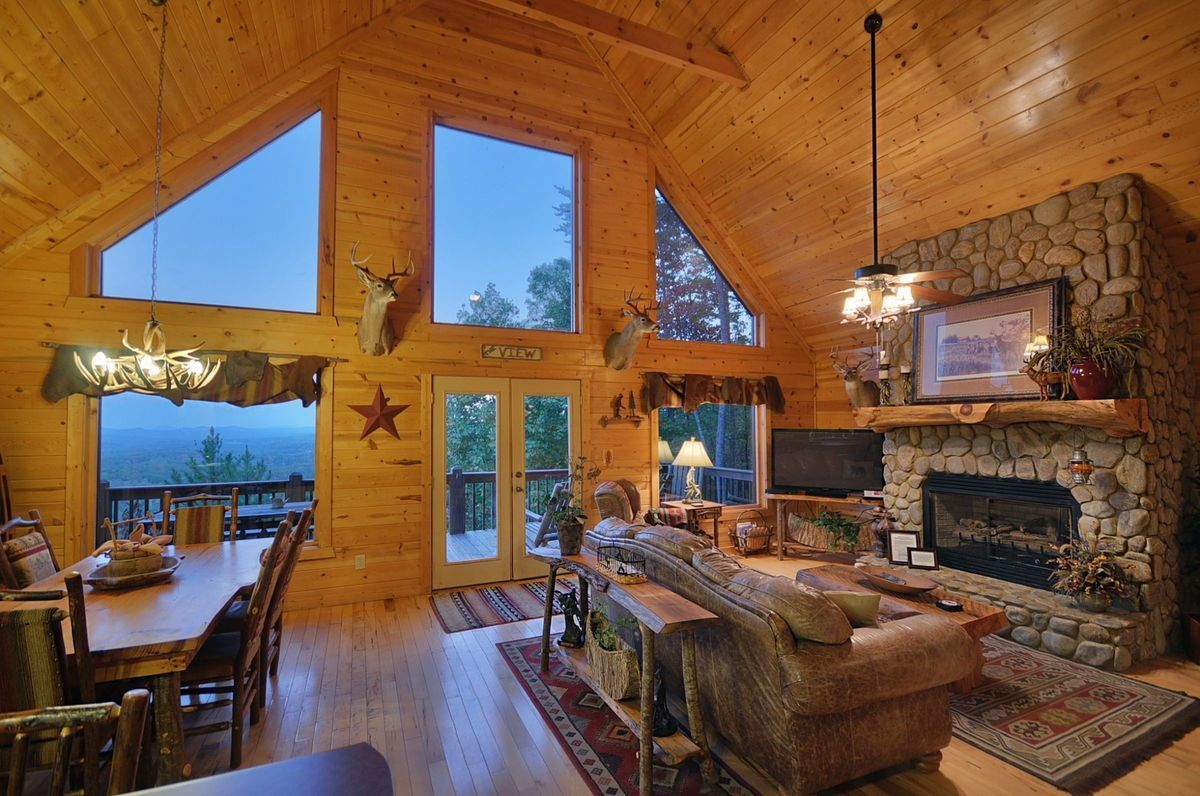 This Smoky Mountain cabin offers an open, cozy living area with floor-to-ceiling views, which affords beautiful views of the mountains and forests.