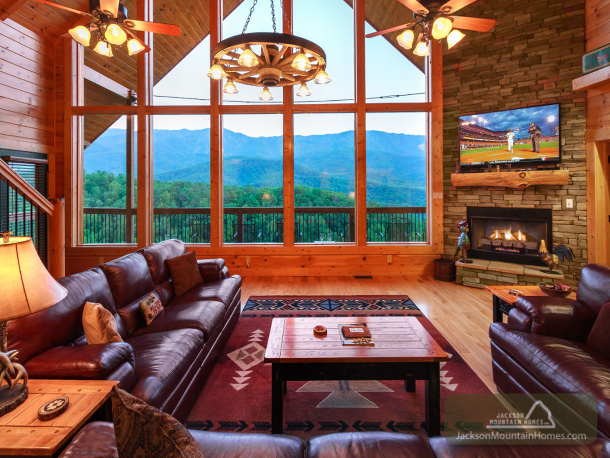 The rustic living room of this Smoky Mountain cabin offers sumptuous leather couches and stunning views of rolling blue mountains.