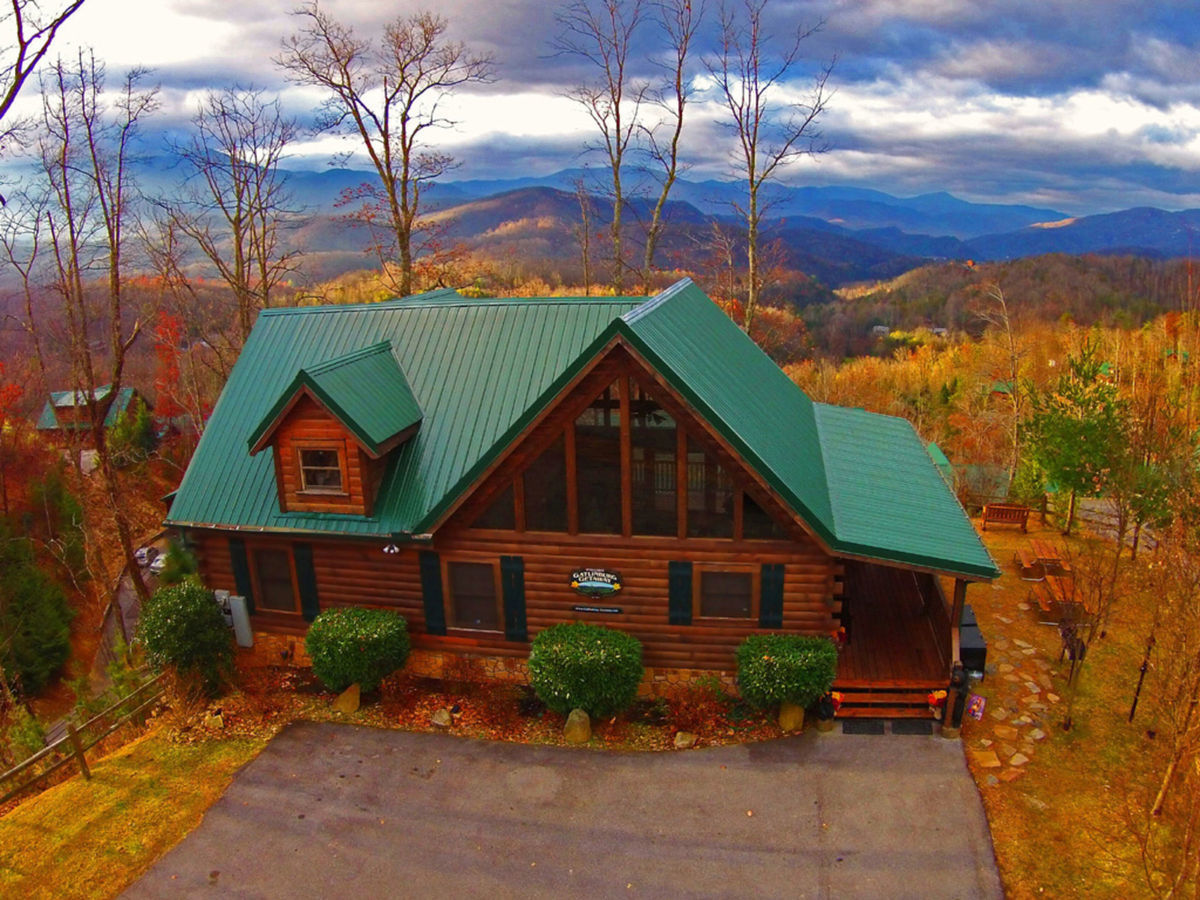 Mountains roll in the distance behind Gatlinburg Getaway, one of our best Smoky Mountain cabins. In the foreground, autumn has changed the leaves of the trees a bright, golden hue.
