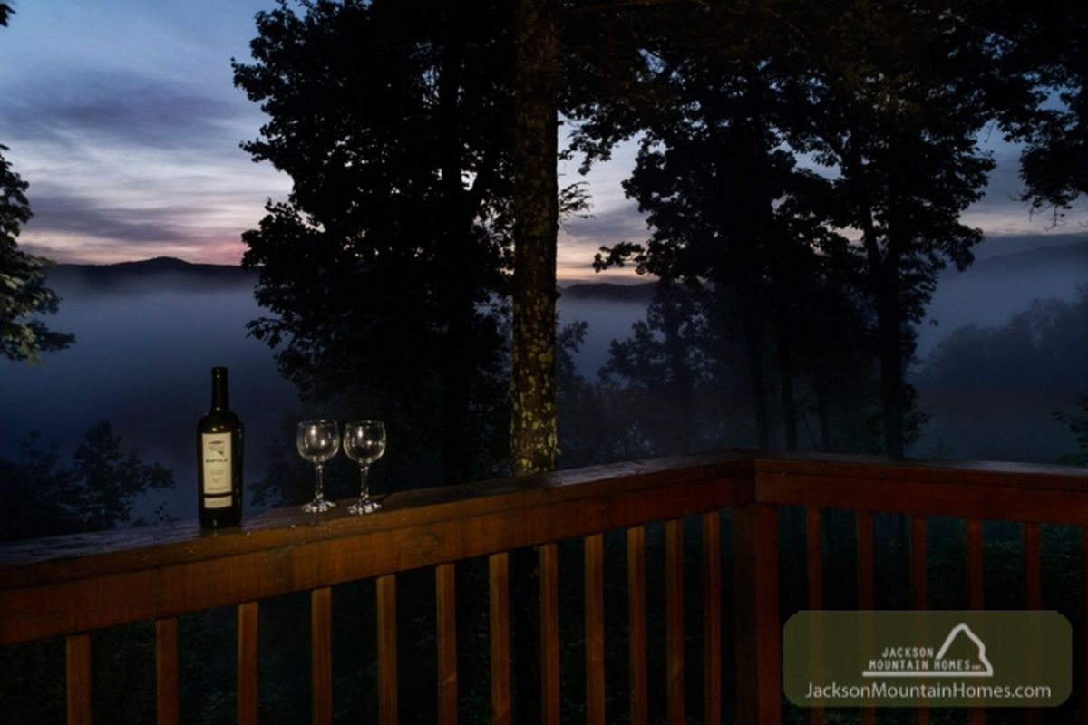 Fog rises amid the blue Smoky Mountains just after sunset with the sky still tinged purple in the distance. On the cabin's patio, a bottle of red wine and two glasses await, adding to the air of romance.