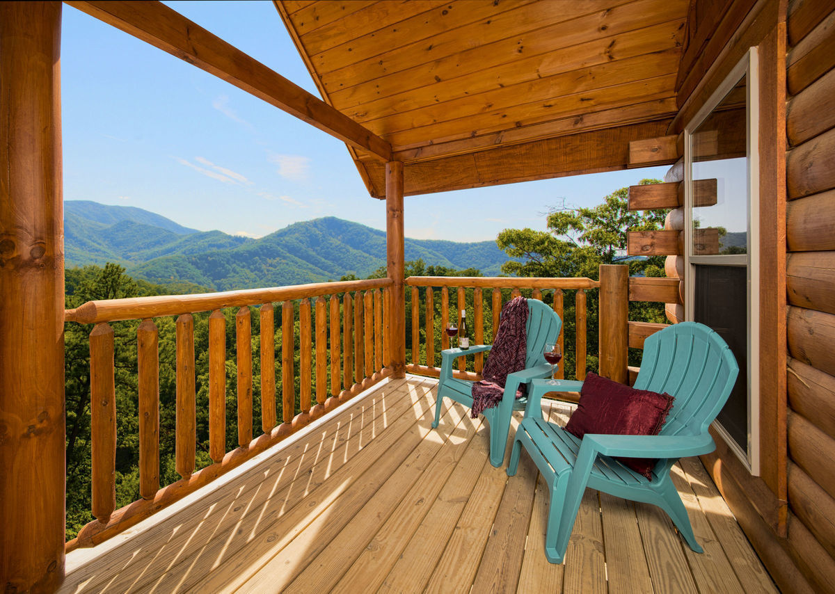 You can see miles of rolling mountains from this rustic balcony, a highlight of this Smoky Mountain cabin.
